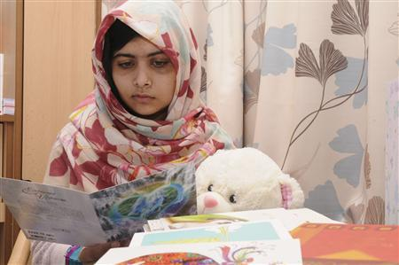 Pakistani schoolgirl Malala Yousufzai reads a card as she recuperates at the The Queen Elizabeth Hospital in Birmingham, in this undated handout photograph released to Reuters on November 8, 2012. REUTERS/Queen Elizabeth Hospital Birmingham/Handout