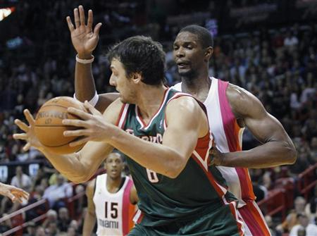 The Miami Heats' Chris Bosh (R) defends against Milwaukee Bucks' Andrew Bogut during their NBA basketball game in Miami, Florida January 22, 2012. REUTERS/Andrew Innerarity