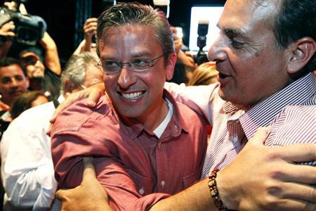 Popular Democratic Party gubernatorial candidate Alejandro Garcia Padilla (L) celebrates his lead over Republican Governor Luis Fortuno in the gubernatorial election, which gives him the tendency to be proclaimed as the new governor, as he arrives at the party headquarters in San Juan November 7, 2012. REUTERS/Ana Martinez