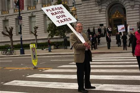 A man with a local group of upper income professionals who call themselves ''Tax-Us'' holds a sign during a rally at City Hall in San Francisco, California April 17, 2012. REUTERS/Robert Galbraith