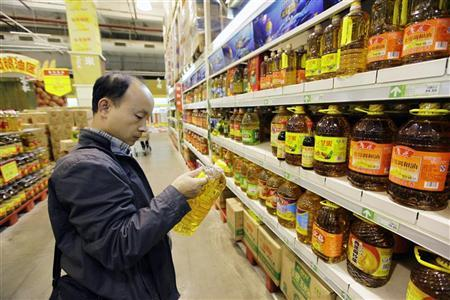 A customer looks at a bottle of cooking oil at a supermarket in Beijing October 15, 2012. REUTERS/Jason Lee
