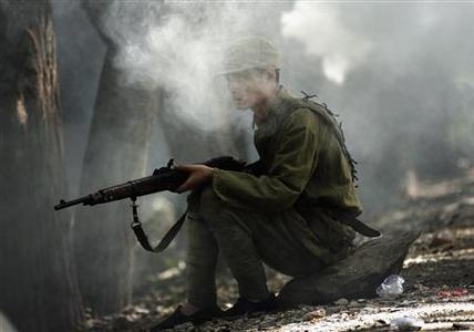 An actor playing a Communist soldier holds his gun as he is covered in smoke during filming of the Chinese television program called 'Chu Guan', meaning 'To Get Out of the Stronghold', at an outdoor film studio located on the outskirts of Beijing in this file picture taken September 13, 2012. REUTERS/David Gray/Files