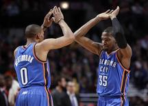 Oklahoma City Thunder point guard Russell Westbrook (0) and Kevin Durant (35) celebrates after a made basket against the Chicago Bulls during the first second of their NBA basketball game in Chicago, Illinois, November 8, 2012. REUTERS/Jeff Haynes