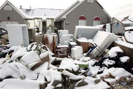 A pile of belongings, coated with a few inches of snow, is seen outside a home in the West Beach Haven community of Manahawkin, New Jersey November 8, 2012 as recovery efforts continue in the aftermath of Hurricane Sandy. REUTERS/Tom Mihalek