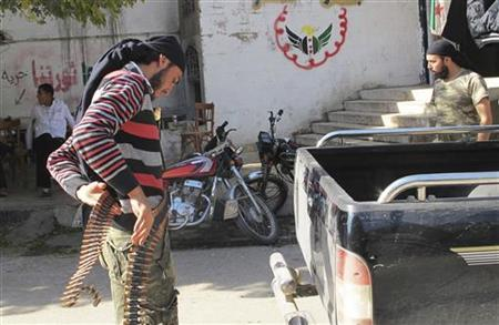 A member of the Free Syrian Army wraps a bullet belt around his waist in Maaret near Idlib Province November 5, 2012. Picture taken November 5, 2012. REUTERS/Abdalghne Karoof (SYRIA - Tags: CONFLICT)