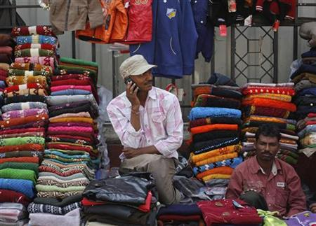 A vendor speaks on his mobile phone as he waits for customers at his roadside shop selling clothes in Mumbai February 2, 2012. REUTERS/Danish Siddiqui/Files