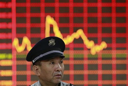 A security guard chats with his colleague (not seen) in front of an electronic board showing stock information at a brokerage house in Huaibei, Anhui province, October 30, 2012. REUTERS/Stringer