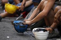 Operai con il loro elmetto in mano prima di entrare in fabbrica. REUTERS/Giampiero Sposito