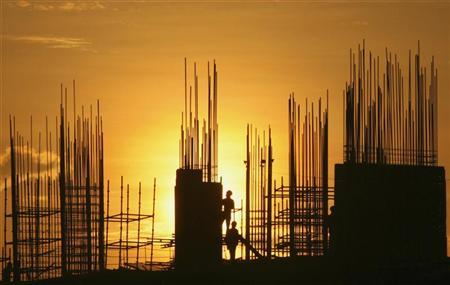 Labourers are silhouetted against the setting sun as they work at the construction site of a residential building in Hyderabad October 5, 2012. REUTERS/Krishnendu Halder/Files