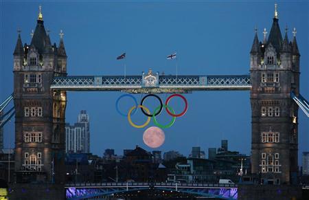 The full moon rises through the Olympic Rings hanging beneath Tower Bridge during the London 2012 Olympic Games August 3, 2012. REUTERS-Luke MacGregor