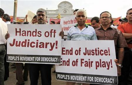 Opposition activists hold up placards during a protest in Colombo November 5, 2012. Hundreds of Sri Lankan lawyers and opposition activities took to the streets of Colombo to protest against a government move to impeach the country's top judge in an increasingly bitter dispute. Lawyers marched from the Supreme Court to the city centre denouncing efforts by President Mahinda Rajapakse's United People's Freedom Alliance party to sack Chief Justice Shirani Bandaranayake. REUTERS/Stringer