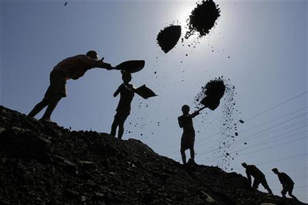 Labourers load coal on trucks at Bari Brahamina in Jammu May 20, 2010. REUTERS/Mukesh Gupta/Files