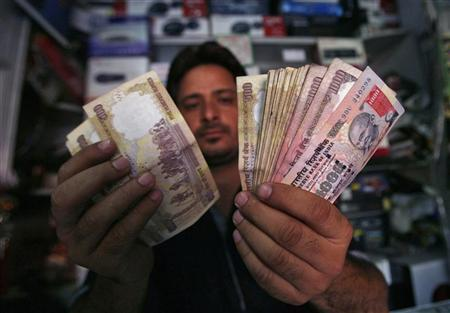A shopkeeper poses for a picture as he counts Indian currency notes at his shop in Jammu May 16, 2012. REUTERS/Mukesh Gupta