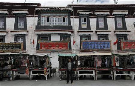 A vendor stands in front of roadside stalls in Lhasa, Tibet Autonomous Region September 15, 2012. REUTERS/Stringer