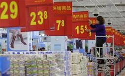 A worker adjusts a price tag at a supermarket in Wuhan, Hubei province, November 9, 2012. China's annual consumer inflation eased to 1.7 percent in October from September's 1.9 percent, official data showed on Friday, leaving policymakers with some scope to tweak monetary policy if necessary to shore up growth. REUTERS/Stringer (CHINA - Tags: BUSINESS) CHINA OUT. NO COMMERCIAL OR EDITORIAL SALES IN CHINA