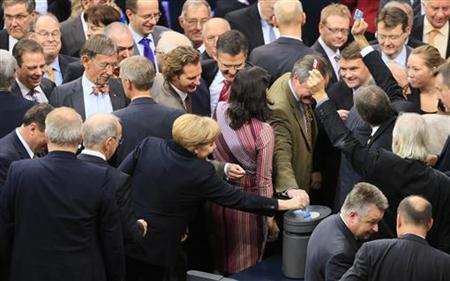 German Chancellor Angela Merkel casts her vote during a session of the lower house of parliament Bundestag in Berlin November 9, 2012. REUTERS/Tobias Schwarz (GERMANY - Tags: POLITICS)