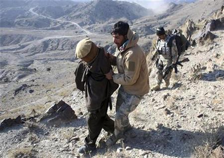 Afghan border policemen escort a detained suspected Taliban fighter near Walli Was in Paktika province near the border with Pakistan November 5, 2012. REUTERS/Goran Tomasevic