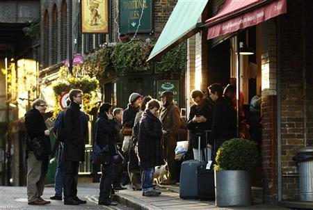 People queue for coffee in Borough Market in London December 9, 2011. REUTERS/Luke MacGregor