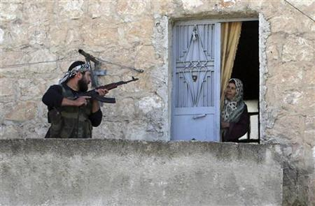 A member of the Free Syrian Army talks to a woman during a patrol to search for pro-government forces in Harem town, Idlib Governorate, in this October 26, 2012 file photo. Picture taken October 26, 2012. REUTERS/Asmaa Waguih/Files