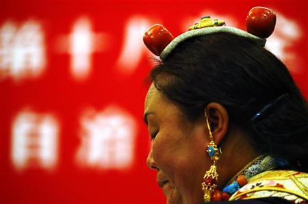 A member of the Tibetan provincial delegation, from China's Tibet Autonomous Region, sits wearing a traditional costume before a meeting with representatives from the National People's Congress (NPC) in the Tibet Room inside the Great Hall of the People, at the 18th National Congress of the Communist Party of China (CPC) in Beijing November 9, 2012. REUTERS/David Gray
