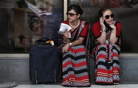 Air India air hostesses sit outside the domestic airport in New Delhi May 25, 2010. REUTERS/Adnan Abidi/Files