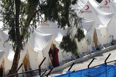 A Syrian refugee woman and a boy stand outside a tent at Yayladagi refugee camp in Hatay province, near the Turkish-Syrian border November 8, 2012. REUTERS/Murad Sezer (TURKEY - Tags: POLITICS SOCIETY IMMIGRATION)