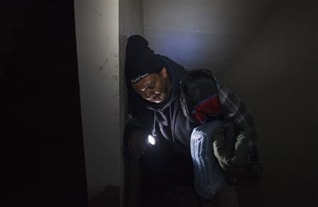 Victor Ocasio pauses to catch his breath as he walks up a darkened stairwell to his 15th floor apartment in New York City Housing Authority (NYCHA) housing that remains without power in the Queens borough neighborhood of Edgemere in New York, November 8, 2012. REUTERS/Lucas Jackson