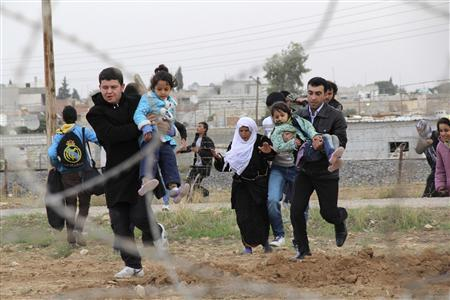 Syrians run as they flee from the Syrian town of Ras al-Ain to Turkish border town of Ceylanpinar, Sanliurfa province November 9, 2012. REUTERS/Stringer