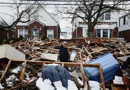 A man walks through piles of debris that have not been removed by the Department of Sanitation outside of homes damaged from flooding that inundated the area during hurricane Sandy in the Queens borough neighborhood of Belle Harbor, New York, November 8, 2012. REUTERS/Lucas Jackson