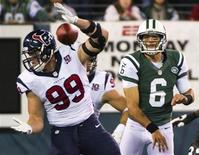 Houston Texans defensive end J.J. Watt (99) blocks a pass by New York Jets quarterback Mark Sanchez (6) in the fourth quarter of their NFL football game in East Rutherford, New Jersey, October 8, 2012. REUTERS/Ray Stubblebine