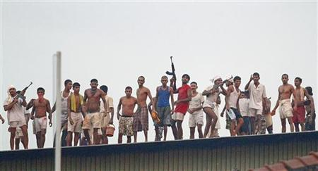 Rioting prisoners from Welikada prison fire weapons from the roof during a clash between Sri Lanka's Special Task Force (STF) at Welikada prison in Colombo, November 9, 2012. REUTERS/Stringer
