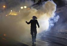 Um manifestante vestindo uma máscara de gás corre através de uma nuvem de gás lacrimogêneo durante protestos violentos na praça de Syntagma no centro de Atenas, na Grécia. Os ministros das Finanças da zona do euro não devem liberar uma nova parcela de empréstimo para a Grécia na segunda-feira, uma vez que não há acordo ainda sobre tornar sua dívida sustentável, mas Atenas deve conseguir mais dois anos para reduzir a dívida, disseram autoridades. 7/11/2012 REUTERS/Yannis Behrakis