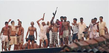 Rioting prisoners fire weapons and cheer from a roof during clashes with Sri Lanka's Special Task Force (STF) at Welikada prison in Colombo, November 9, 2012. REUTERS/Stringer