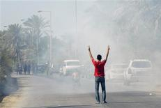An anti-government protester gestures as he stands in tear gas fired by riot police, as he tries to walk towards the village of Diraz, west of Manama November 9, 2012. REUTERS/STRINGER