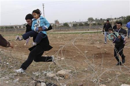 Syrians jump over barbed wire as they flee from the Syrian town of Ras al-Ain to the Turkish border town of Ceylanpinar, Sanliurfa province, November 9, 2012. REUTERS/Stringer