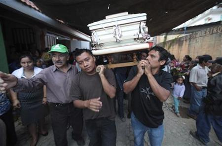 People carry to the cemetery the coffin of one of the four members of the De Leon family, who were killed during a landslide triggered by a 7.4-magnitude earthquake, in El Recreo, in the outskirts of San Pedro Sacatepequez in the San Marcos region, about 250 km (155 miles) away of Guatemala City, November 9, 2012. REUTERS/William Gularte