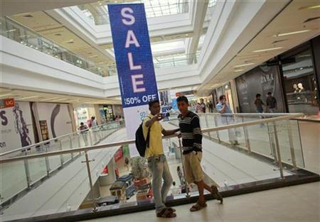 A shopper takes a photograph with his mobile phone inside a shopping mall in Mumbai July 14, 2012. REUTERS/Danish Siddiqui
