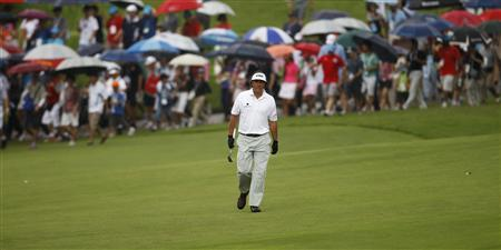 Phil Mickelson of the U.S. walks down the eighth fairway as spectators carrying umbrellas follow in the light drizzle during the rain-delayed second round of the Barclays Singapore Open golf tournament in Sentosa November 10, 2012. REUTERS/Edgar Su