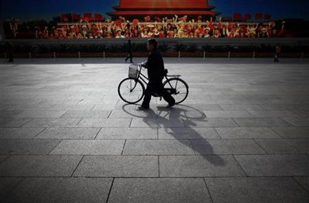 A man walks with his bicycle in front of a screen showing propaganda displays near the Great Hall of the People at Beijing's Tiananmen Square, November 7, 2012. REUTERS/Carlos Barria