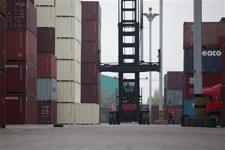 Workers drive a machine in a shipping container area at the Port of Shanghai November 10, 2012. China's export growth quickened in October and the pace of imports held steady, adding to signs the domestic economy is stabilising and weakening the case for further policy measures to boost activity. REUTER/Aly Song
