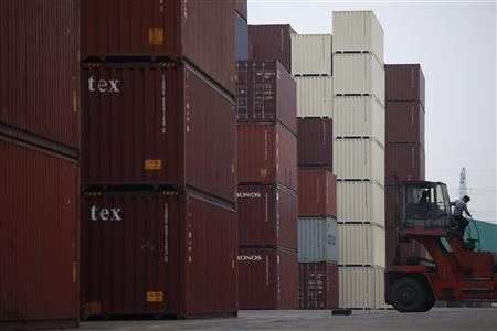 Workers are seen in a machine in a shipping container area at the Port of Shanghai November 10, 2012. REUTER/Aly Song