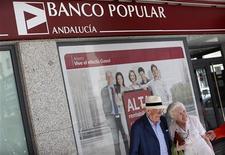 Banco Popular dijo el sábado que realizará su ampliación de suscripción preferente por 2.500 millones de euros con la que trata de evitar la inyección de fondos públicos a un precio de 0,401 euros, lo que supone un descuento de en torno al 64 por ciento respecto al cierre del viernes y un 76 por ciento antes del anuncio de la operación. En la imagen, una pareja de ancianos sonríe junto a una sucursal del Banco Popular en la capital andaluza Sevilla, el 3 de octubre de 2012. REUTERS/Marcelo del Pozo