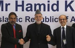 Afghanistan's President Hamid Karzai (C) shakes hands with India's Trade Minister Anand Sharma (L) and Chairman of the Godrej Group Adi Godrej during a business conference in Mumbai November 10, 2012. Karzai is on a five-day state visit to India. REUTERS/Vivek Prakash
