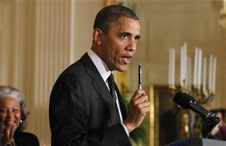 U.S. President Barack Obama holds up his pen as he delivers a statement on the U.S. ''Fiscal Cliff'' in the East Room of the White House in Washington, November 9, 2012. REUTERS/Jason Reed