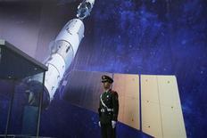China planea lanzar su nave espacial Shenzhou 10 a comienzos de junio de 2013, dijo el sábado uno de los altos funcionarios a cargo del programa espacial tripulado e informó la agencia de noticias oficial Xinhua. En la imagen, de 2 de noviembre, un oficial de la policía paramilitar permanece de pie en la exposición sobre la nave espacial tripulada lanzada por China en el Museo de Ciencia y Tecnología de Shanghai. REUTER/Aly Song