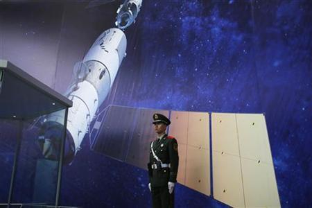 A paramilitary police officer stands guard during ''China's manned spacecraft'', at an exhibition related to Shenzhou-9 at Shanghai Science and Technology Museum in Shanghai November 2, 2012. REUTER/Aly Song