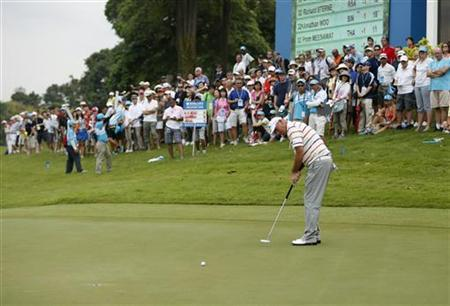 Thomas Bjorn of Denmark putts on the ninth hole during the rain-delayed second round of the Barclays Singapore Open golf tournament in Sentosa November 10, 2012. REUTERS/Edgar Su