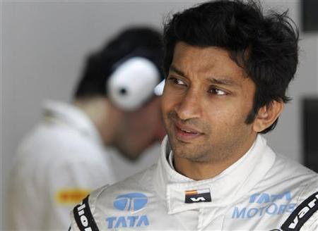 HRT Formula One driver Narain Karthikeyan talks to crew members in his team garage during the first practice session of the Indian F1 Grand Prix at the Buddh International Circuit in Greater Noida, on the outskirts of New Delhi, October 26, 2012. REUTERS/Vivek Prakash/Files