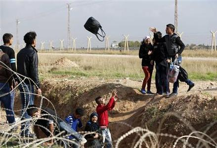 Syrians throw their belongings while trying to cross a ditch after crossing from the northern Syrian town of Ras al-Ain to Turkey in the border town of Ceylanpinar, Sanliurfa province, November 10, 2012. REUTERS/Murad Sezer