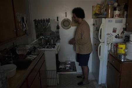 Resident Daniel Quarles warms himself at his stove in the Red Hook Houses in the Brooklyn Borough of New York, November 9, 2012. Residents are going into a second week without heat or electricity. Fuel shortages and power outages lingered more than week after one of the worst storms in U.S. history flooded homes in coastal neighborhoods. REUTERS/Keith Bedford